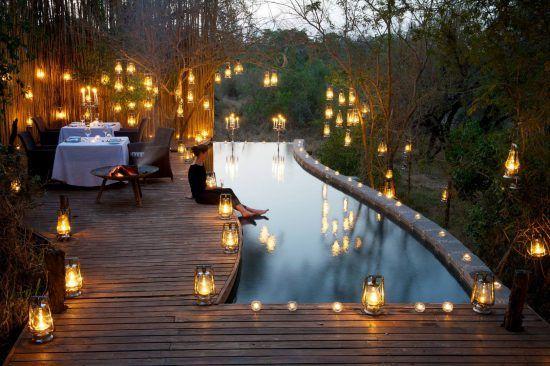 Dîner romantique à la bougie au bord de la piscine en safari à Londolozi, Afrique.