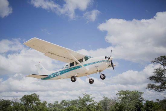 Ein Kleinflugzeug hebt vor blauem Himmel mit kleinen weißen Wolken ab
