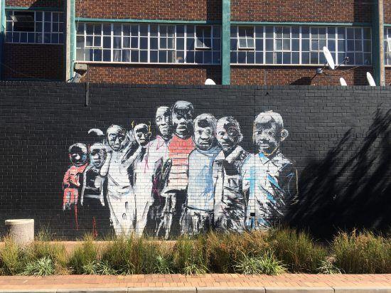 Buntes Graffiti, das eine Menschengruppe zeigt, auf einer Mauer aus Backstein