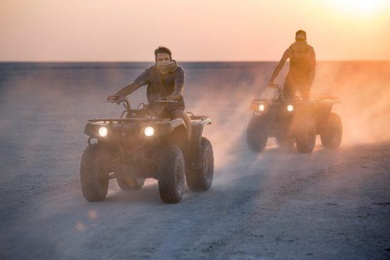 Zwei junge Männer düsen bei Sonnenuntergang auf Quad Bikes durch die Wüste
