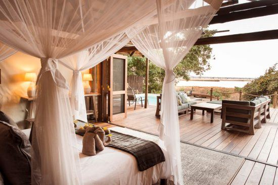 Ein großes Bett in einem luxuriösen Zelt, das einen Blick auf den Fluss bietet – die schönsten Unterkünfte in Sambia