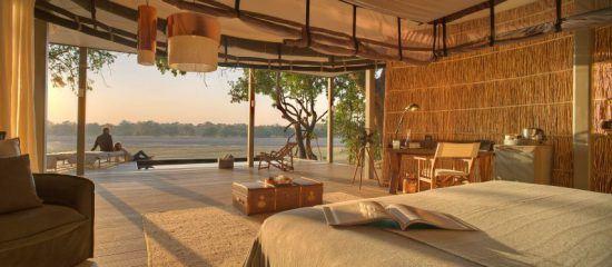 Blick aus einem luxuriösen Zelt auf eine private Holzterrasse, ein Flussufer und den Busch