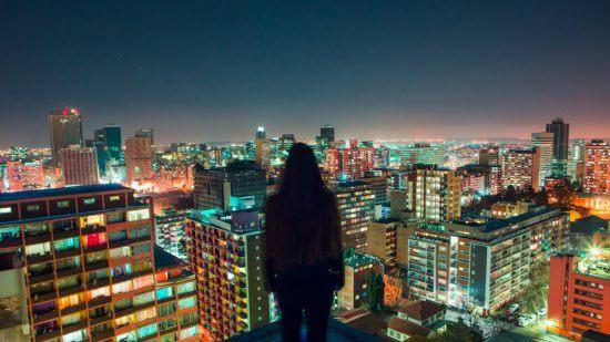 Frau vor Skyline einer Grosstadt bei Nacht