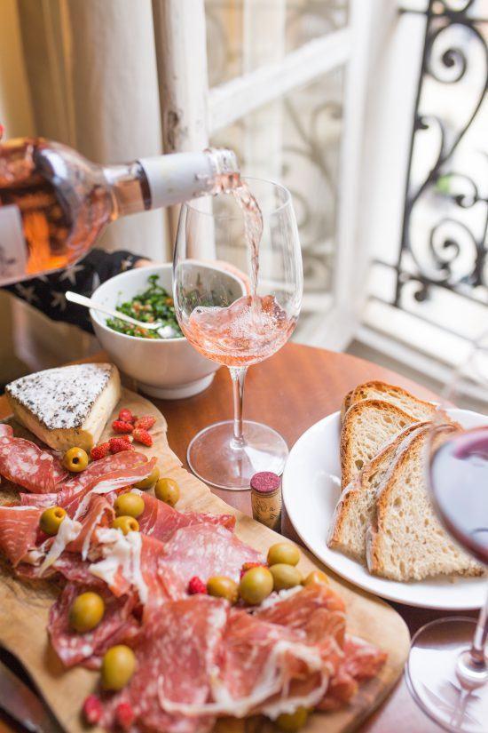 Vinho rosé sendo servido em uma taça, em uma mesa de frios