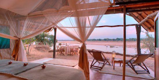 Offenes Zelt mitten in der afrikanischen Wildnis mit Blick aufs Wasser