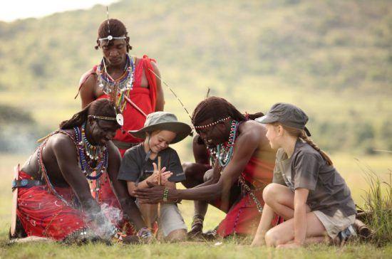 Einheimische bringen Kindern bei, wie man ein Feuer macht