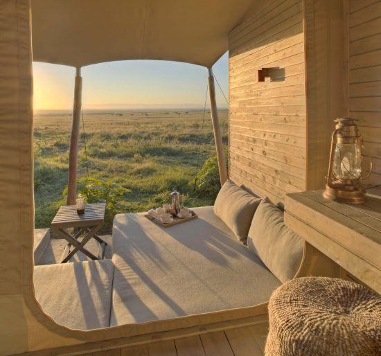Blick aus einem luxuriösen Zelt auf den Sonnenaufgang über der Savanne