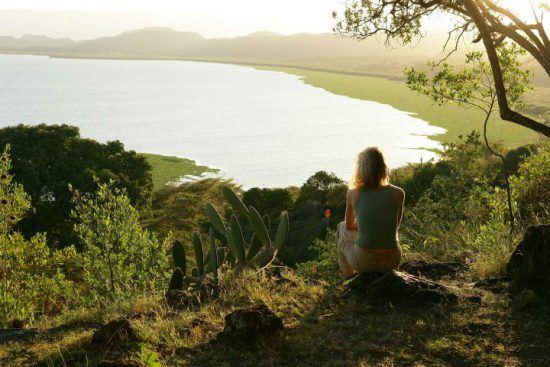 Frau sitzt auf einem Stein und genießt den Blick über einen See in Kenia