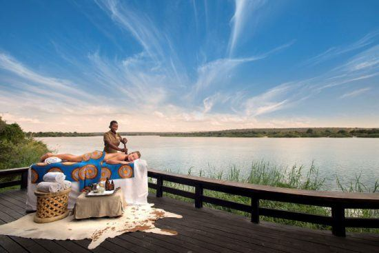 Eine Frau genießt eine Massage unter freiem Himmel am Ufer des Sambesi in Sambia