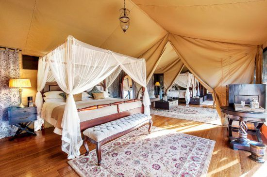 A bed inside a stylish tent at Sand River Masai Masai