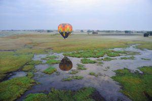 Ein bunter Heißluftballon fliegt über die traumhafte Landschaft Sambias