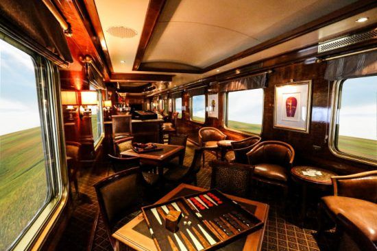 Die gemütliche Lounge des Blue Train mit großen Fenstern und dunklen Möbeln