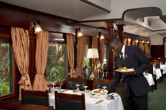 Garçom retira prato de mesa na área de jantar do Rovos Rail