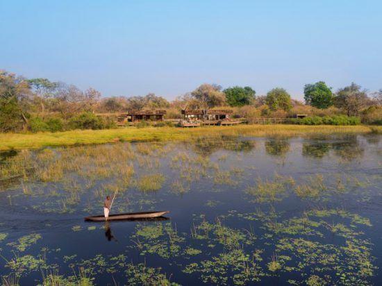 Ein Mann in einem traditionellen Kanu gleitet vor einer Lodge über das Wasser des Okavango Delta