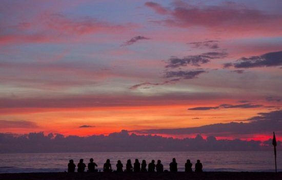 Gruppe sitzt am Strand bei Sonnenuntergang