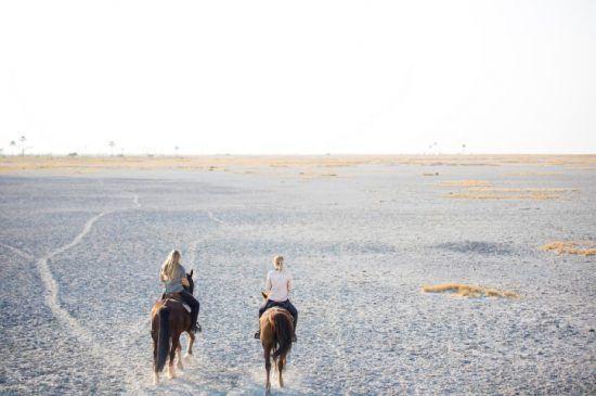 Zwei Frauen reiten in den weißen, kargen Makgadikgadi Salzpfannen aus