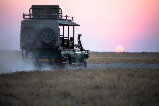 Ein vollbepackter Jeep fährt in der offenen Ebene Botswanas in einen rosa Sonnenuntergang