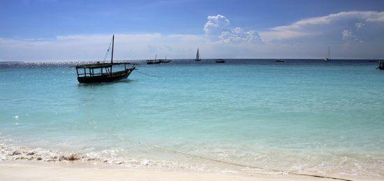 Ein Boot in türkisblauem Wasser vor Sansibar