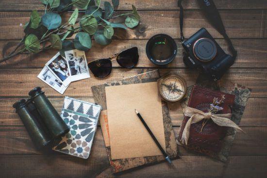 Auf einem Tisch liegen Reisedokumente, Sonnenbrille, Kompass, Kamera, Fotos und Schreibzubehör bereit