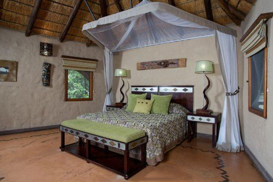 Ein Doppelbett mit Moskitonetz in einer traditionellen Safari-Lodge
