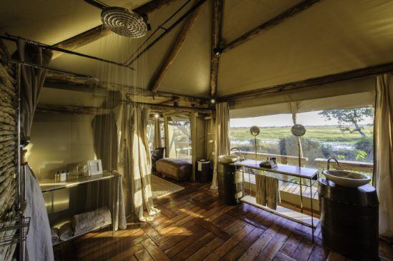 Dusche inmitten eines großen Safari-Zelts, das offen ist und einen Ausblick auf die Natur bietet