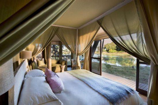 Frisch gemachtes Bett in einem offenen Zelt mit Blick auf eine Wasserlandschaft
