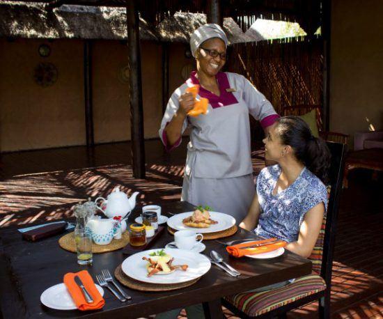 Eine Frau serviert einer jungen Frau Frühstück und lächelt dabei