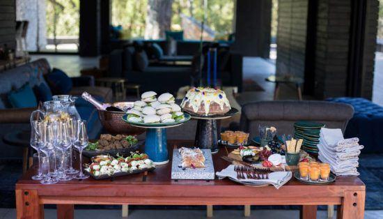 Eine große Auswahl an leckeren Snacks und Getränken auf einem Tisch vor einer Luxuslodge - SIlvan Safari
