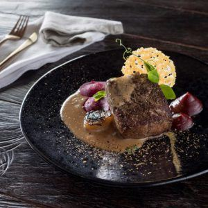 Nahaufnahme eines Steaks auf einer Soße mit einem Käsecracker auf einem schwarzen Teller
