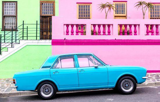 Voiture bleu électrique face aux maisons colorées de Bo Kaap au Cap.