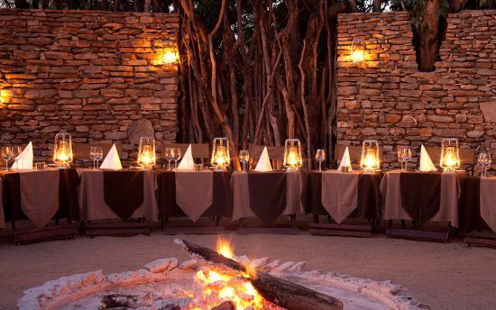 Dinner im Sabi Sand Game Reserve: Festlich gedeckte Tische in einer Boma mit Lagerfeuer in der Mitte