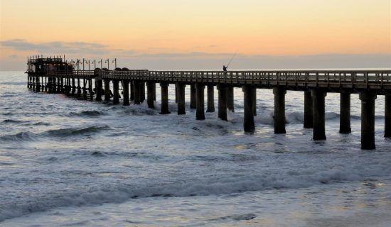 Ein Pier an einem traumhaften Strand vor einem farbenfrohen Sonnenuntergang in warmen Tönen