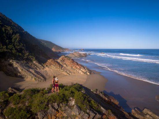 Ein Paar steht auf einem Hügel und blickt auf einen Sandstrand bei blauem Himmel