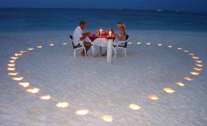 Ein Paar genießt ein romantisches Dinner am Strand umgeben von Kerzen, die ein Herz bilden