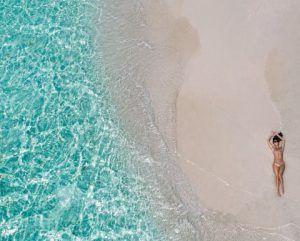 Eine Frau im Bikini liegt an ein einem einsamen Strand nahe der kristallklaren Brandung