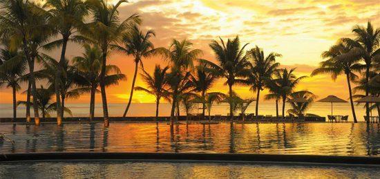 Sonnenutergang in Orangetönen hinter Palmen am Strand