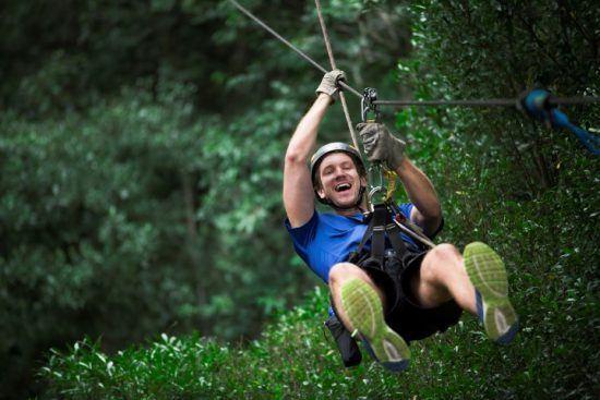 Ein junger Mann hat großen Spaß beim Ziplining im Wald