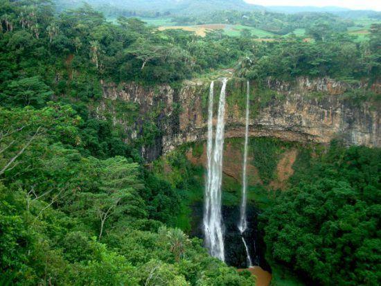 Ein schmaler Wasserfall in einer grün-tropischen Landschaft