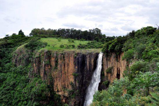 Ein Wasserfall zwischen rötlich-orangenen Felsen und grüner Natur - die schönsten Wasserfälle in Afrika