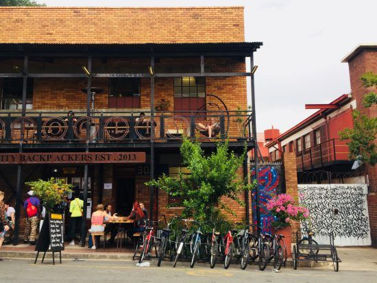 Außenansicht eines Backsteingebäudes mit Cafe und Fahrradständer in Maboneng, Johannesburg