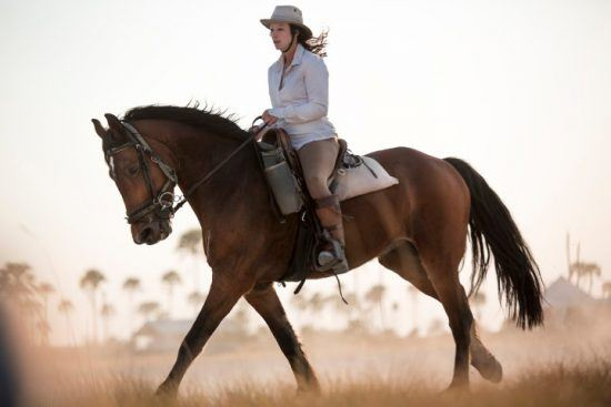 Eine Frau mit Hut reitet durch die afrikanische Wildnis