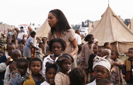"""Atriz Sophie Okonedo cercada por crianças no set de """"Hotel Ruanda"""""""