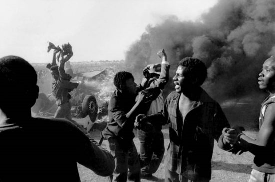 Zwei Schwarze im Vordergrund bei einem Protest, Rauch im Hintergrund