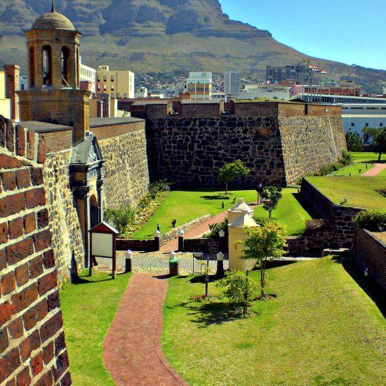 Eine Festungsmauer mit einem Glockentur, dahinter der Tafelberg