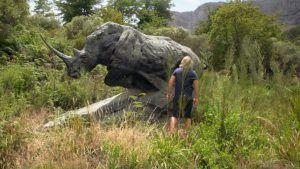 Dylan Lewis face à sa sculpture de rhinocéros