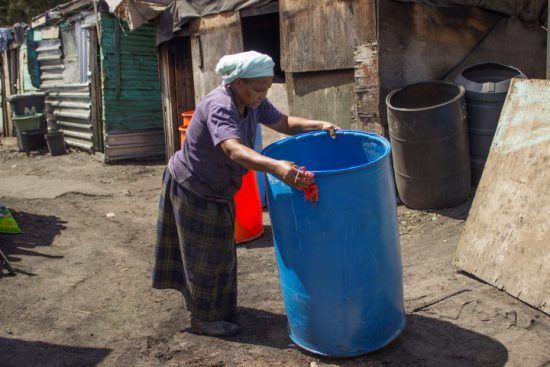Eine Frau putzt eine große blaue Tonne