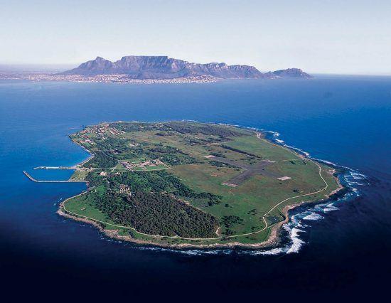 Eine Insel umrandet von Meer, dahinter erkennt man den Tafelberg