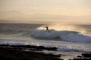 Un surfista en la costa de Jeffrey's Bay, Sudáfrica