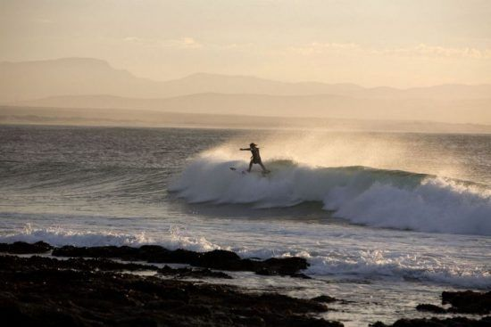Surfista en la costa de Jeffrey's Bay, Sudáfrica