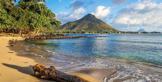 Ein goldener Strand mit Palmen und Bergen im Hintergrund